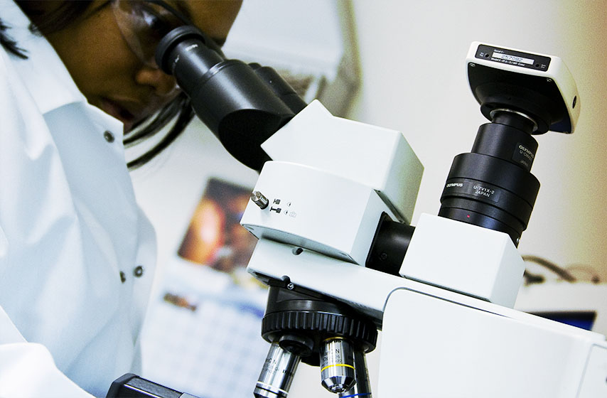Lab technician using microscope in DNA Solutions forensics dna analysis laboratory